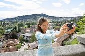 Selfie girl - Asian woman taking self portrait photography picture with smartphone at view point in Bern, Switzerland. Smart phone and travel.