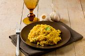 Risotto With Saffron On Wooden Table