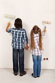 Kids painting their room together - using roller brushes