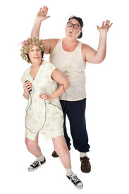 image of wife-beater  - Wife dancing to music with an annoyed husband - JPG