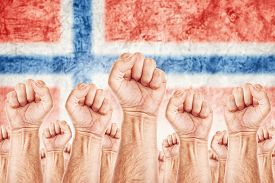 foto of labourer  - Norway Labour movement workers union strike concept with male fists raised in the air fighting for their rights Norwegian national flag in out of focus background - JPG
