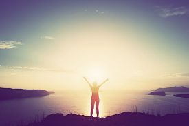 pic of greek-island  - Happy woman with hands up standing on cliff over sea and islands at sunset - JPG