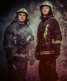 stock photo of firefighter  - Two firefighters with helmet and axe in a smoke - JPG