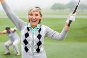 stock photo of ladies golf  - Lady golfer cheering at camera with partner behind on a foggy day at the golf course - JPG