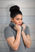 picture of shivering  - Pretty girl in winter jumper shivering against wooden planks - JPG