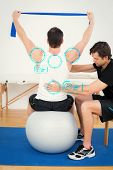 picture of physical therapist  - Man on yoga ball working with a physical therapist against fitness interface - JPG