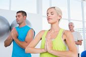 stock photo of joining hands  - Fit people meditating with hands joined in gym class - JPG