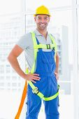 picture of harness  - Portrait of construction worker wearing safety harness in bright office - JPG