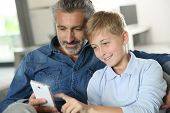 stock photo of daddy  - Daddy with son playing with smartphone - JPG
