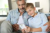 image of daddy  - Daddy with son playing with smartphone - JPG