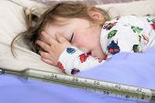 picture of high fever  - Mercury thermometer showing high temperature and a little sick girl in bed - JPG