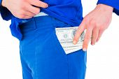 foto of handyman  - Handyman putting money in his pocket on white background - JPG
