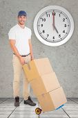 image of trolley  - Happy delivery man pushing trolley of boxes against grey room - JPG