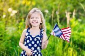 stock photo of waving  - Pretty little girl with long curly blond hair holding an american flag waving it and laughing on sunny day in summer park - JPG