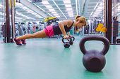 image of health center  - Portrait of beautiful woman doing pushups over black iron kettlebells in a crossfit training on fitness center