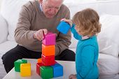 pic of grandpa  - Grandpa and child playing with color cubes - JPG