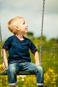 foto of swings  - Little blonde boy having fun at the playground - JPG