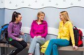 stock photo of training room  - Happy girls are talking in locker room before fitness training - JPG
