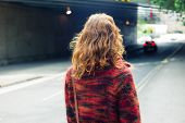 image of underpass  - A young woman is walking on the street near an underpass - JPG