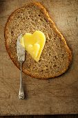 stock photo of ghee  - ghee or melted butter in heart shape on wholemeal bread - JPG