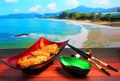 pic of deep  - traditional Vietnam deep fried shrimp and pork rolls in breadcrumbs served on a wood table top by the beach - JPG