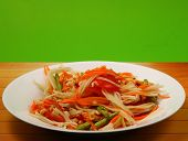 pic of green papaya salad  - thai hot papaya salad with a green background on a wood table top - JPG