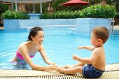 stock photo of crying boy  - Crying fearful boy does not want to swim in the pool with his mother - JPG