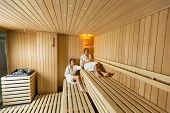picture of sauna woman  - Young women relaxing on the bench in sauna - JPG