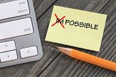 image of impossible  - changing impossible to possible on a note with desk background - JPG