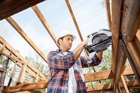 picture of timber  - Low angle view of male construction worker using electric saw on timber frame at site - JPG