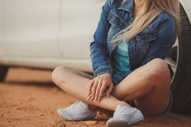 image of denim wear  - A young woman wearing a blue denim jacket and short denim shorts blue, blue shirt and white sneakers, posing sitting on a road near the luxurious white expensive car in a field in summer.