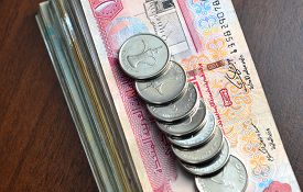 image of dirham  - Many one dirham coins placed on stack of hundred dirham notes - JPG