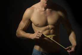 stock photo of nipples  - Closeup of young naked guy in jeans with sexual strong muscular beautiful tan body with sexy chest and nipples holding yellow tape measure round waist standing on black background horizontal picture - JPG