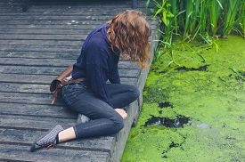 picture of algae  - A young woman is sitting on a wooden deck by a dirty pond with algae in a forest - JPG